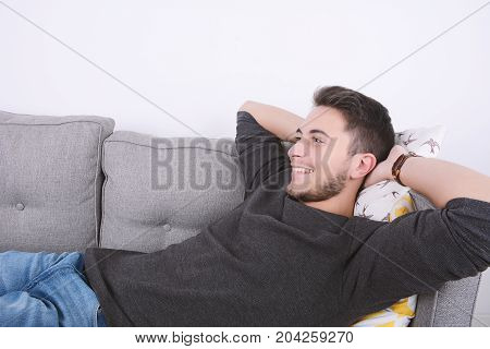 Attractive young man llying and relaxed on couch. Indoors.