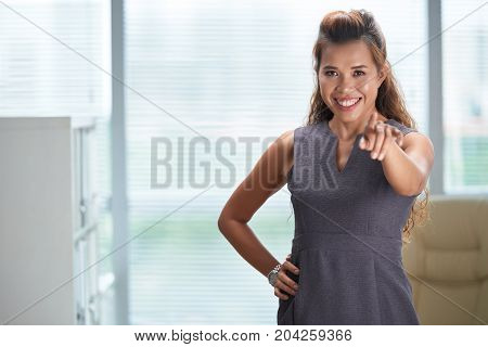Beautiful Asian business lady pointing at you