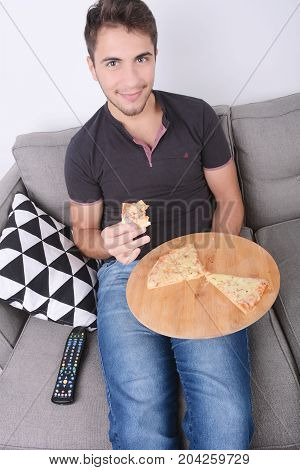 Attractive young man eating pizza on couch. Indoors.