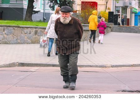 Zhytomyr, Ukraine - May 9, 2015: old poor man walking by the streets at big boots
