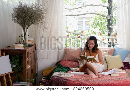 Vietnamese young woman resting in her room with good book