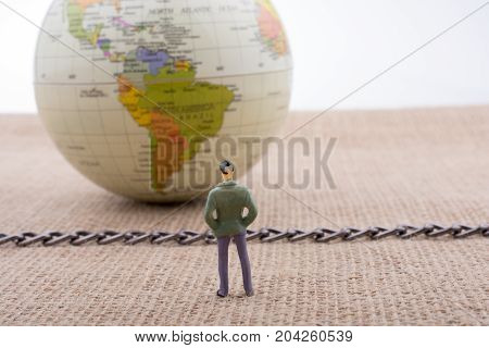 Figurine And Globe With A Chain In The Middle