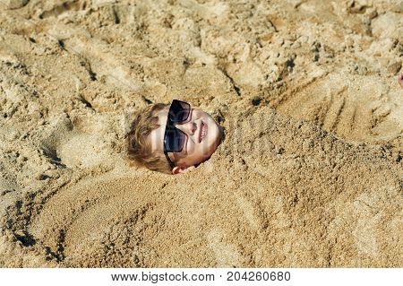 Little boy buried in the sand on the beach