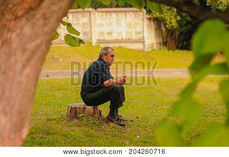 Zhytomyr, Ukraine - September 03, 2015: Senior man with stick sitting on firewood outdoors