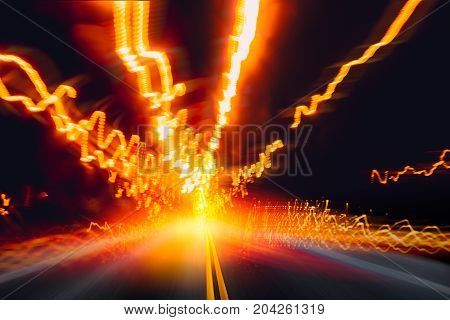 high speed car driving on night highway road with light trail motion effect