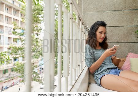 Atractive Vietnamese girl texting and drinking tea on balcony