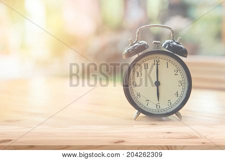 Retro clock at 6 o'clock on wood table foreground with blur light nature background