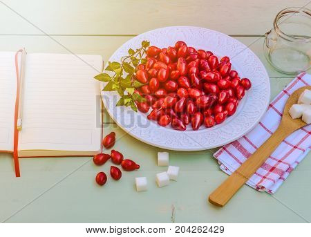Fresh red cornel berries on white plate, preparing for homemade cornelian cherry jam, surrounded by jelly jar, flax napkin, vintage spoon, sugar, spices,notebook for recipes, rustic wooden background.