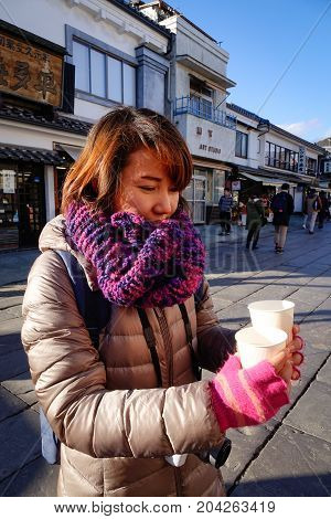 An Asian Woman Holding Cup Of Tea On Street