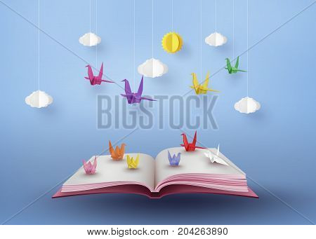 origami made colorful paper bird flying over open book and blue sky with clound . paper art and craft style.