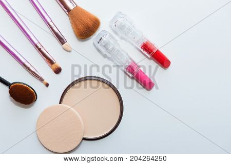 Make up and cosmetic beauty products arranged on a light purple background with empty space at side
