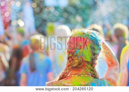 Color festival the girl strewn with multi-colored paints view from back