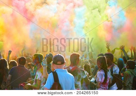 Color festival youth throws up multicolored powdery paint
