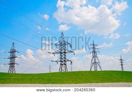 High-voltage supports on the green hill against the sky