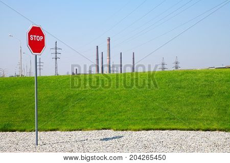 Industrial Area High-voltage supports stop sign and smokestacks against the sky