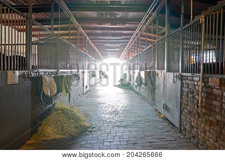 Stable with open gates and bundles of hay on the floor