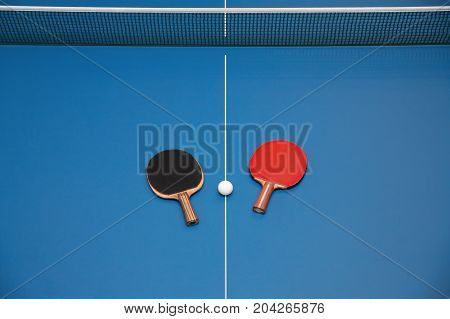Rackets for table tennis of red and black color and a ball on a tennis table view from above