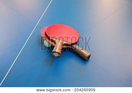 Rackets for table tennis of red color and a ball on a tennis table view from above