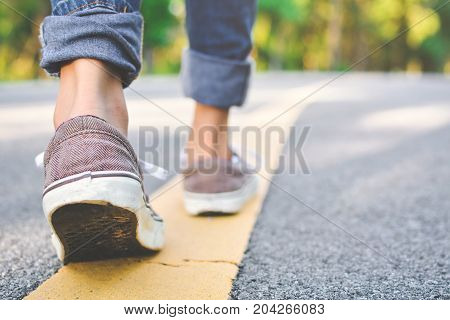Feet of girl walking in the road and forest background Relax time on holiday concept travel color of vintage tone and soft focus