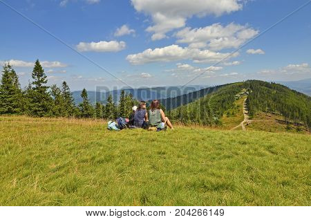 Bielsko-Biała, Silesia, Poland - July 29: a group of women tourists with a kid admiring the view from the top of Klimczok  in Beskidy mountains to the Klimczok mountain chalet and a hiking trail on July 29, 2017 in Bielsko-Biała, Silesia, Poland.