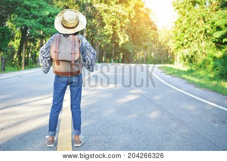Happy Asian girl backpack in the road and forest background Relax time on holiday concept travel color of vintage tone and soft focus