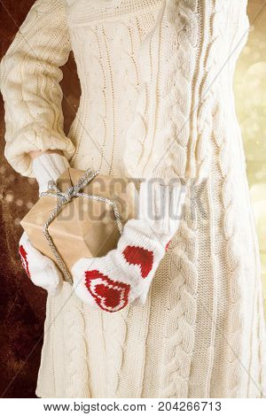 Woman holding gift box behind her back. Christmas or Valentine's day concept. Vintage style