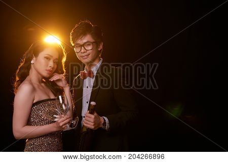Beautiful young Vietnamese couple with champagne bottle and flutes