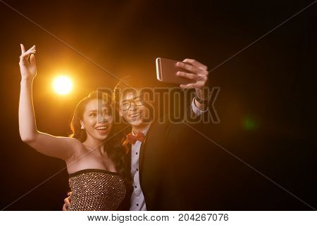 Laughing Vietnamese couple taking selfie at the party