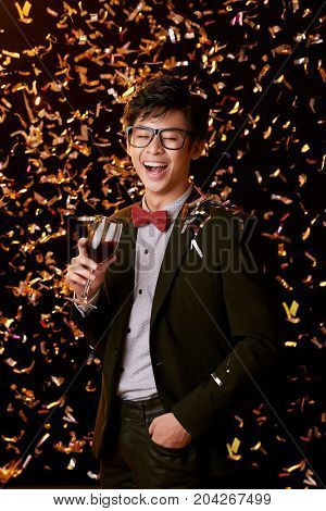 Laughing Asian young man standing under falling confetti with glass of wine