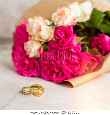 Wedding rings and roses bouquet. Valentines day card. shallow depth of field. Toned image