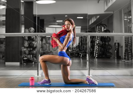 Fitness girl with red towel and shaker relaxing in the gym. A slim athletic woman wears blue sports clothes.