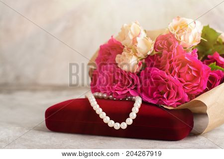 Pearl necklace on red velvet box and pink roses bouquet. Shallow depth of field. Toned image