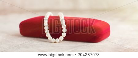 Pearl necklace on red velvet box. Shallow depth of field. Toned image