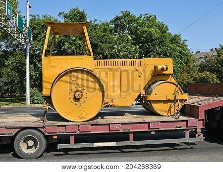 Old steamroller on a trailer vehicle in summer