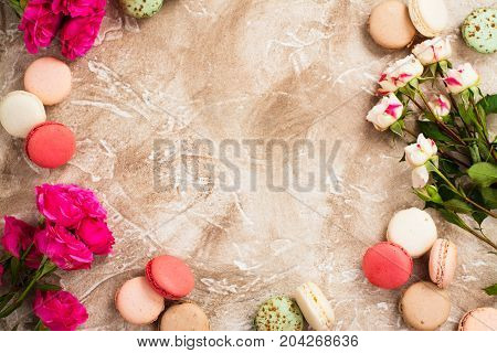 Valentines day background with flowers and macaroons almond cookies. Space for text. Top view