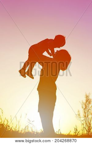 Silhouette of a happy woman with her child at sunset.