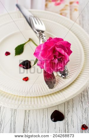 Valentines day table setting with white plates, hearts and rose. Space for text. Holidays background