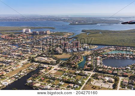 Aerial view of city and gulf Cape Coral Florida. Typical architecture of South Florida. Large houses built on the banks of canals canals into the sea.