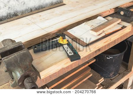 Carpenter tools wood planks clamp notebook on a rusty table.