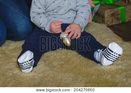 little boy hold christmas tree toy in hands while sitting on the floor