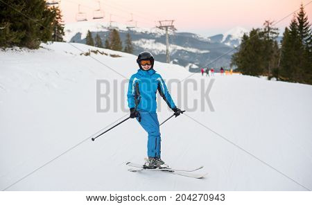 Smiling Woman Wearing Helmet, Blue Sportswear And Ski Goggles Riding Skis On The Snowy Mountain At A