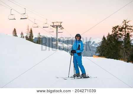 Young Beautiful Female On Ski Holiday In Mountains Looking At The Camera And Smiling. Woman At Ski R