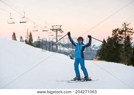 Girl Enjoying Ski Holiday Standing On The Snowy Mountain And Raised Her Hands Up. Woman At Ski Resor