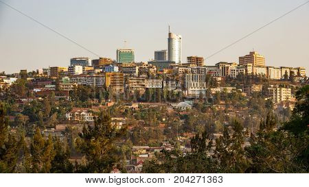 Wide shot of Kigali downtown in Rwanda with modern buildings and antique huts