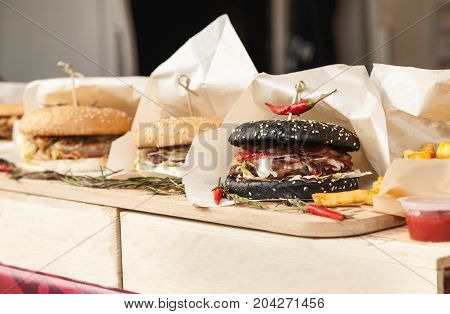 Many Hamburgers Wrapped In Paper On A Wooden Table