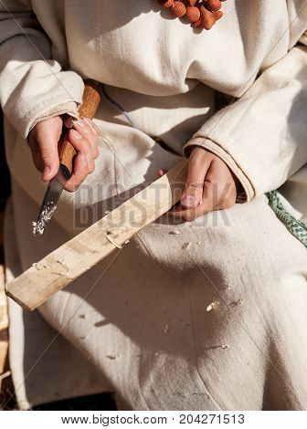 Female Carpenter Hands Holding Knife And Wooden Plank