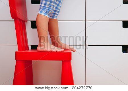 kids safety - little girl climb on chair
