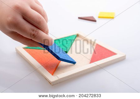 Hand Holding A Missing Piece In A Tangram Puzzle
