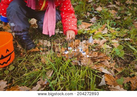 little girl searching for halloween eyeballs in fall, kids trick or treat