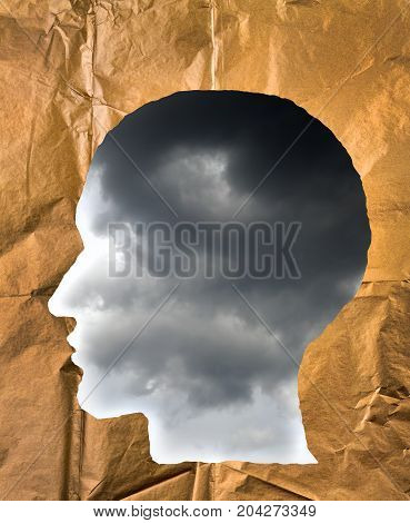 Crumpled paper shaped as a human head. Stormy sky inside the head. Negative and imagination concept.